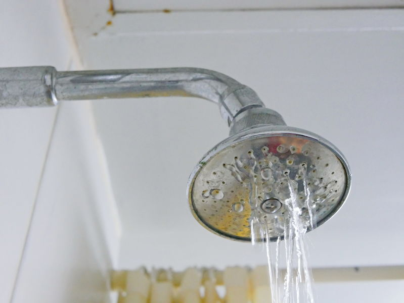 Close up of a partly clogged shower head in a bathroom, causing it to putting out so little water