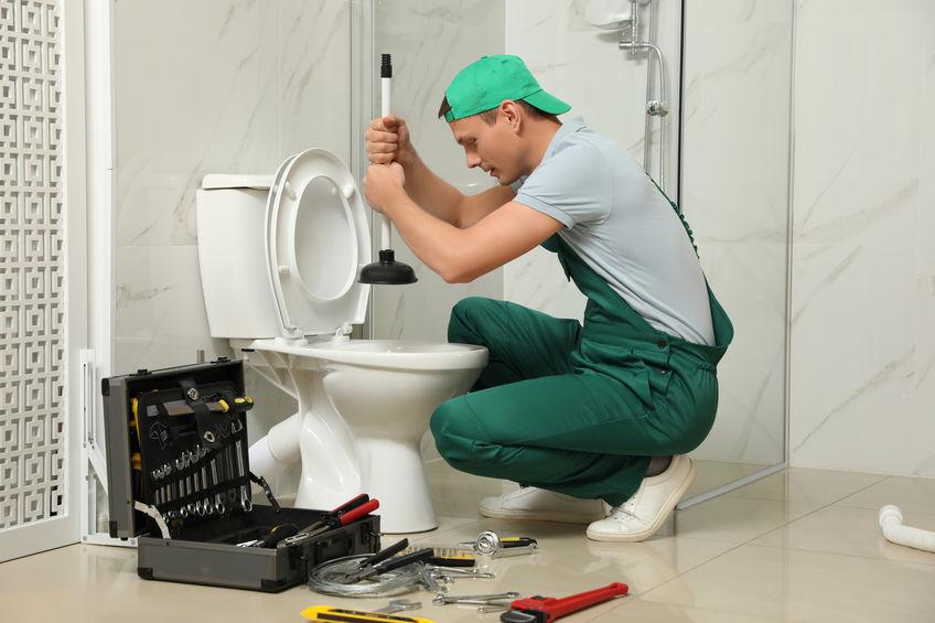 Professional plumber unclogging drain of toilet bowl in bathroom